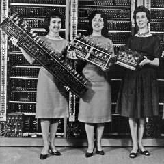 scientists holding early computer parts